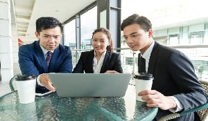 Social Post-Group of business people discuss about the data showing on laptop computer